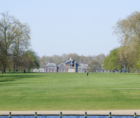 watts: LONDON, UK - APRIL 22: Kensington Palace seen from the Serpentine lake on a sunny spring day, with George Frederic Watts Editorial