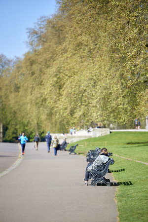 kensington: LONDON, UK - APRIL 22: Kensington Park visitor sitting on bench on sunny spring day, with people walking in the pavement in the tree lined blurry background. April 22, 2015 in London.