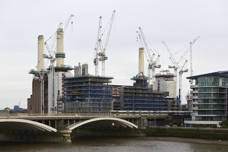 battersea: LONDON UK  MAY 01: Battersea power station surrounded by cranes and scaffoldings. May 01 2015 in London. The chimneys of the emblematic structure are being rebuilt as part of its redevelopment. Editorial