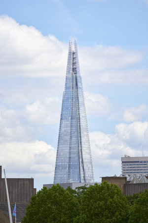 sky scraper: LONDON UK  JUNE 15: The Shard seen from the South Bank with cloudy blue sky in the background. June 15 2015 in London.