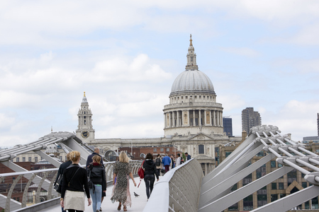 millennium bridge: LONDON, UK - JUNE 23: Dome of Saint Pauls cathedral, with people crossing Millennium Bridge in the foreground. June 23, 2015 in London. Editorial