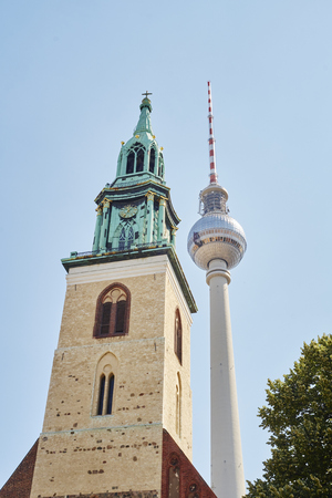 juxtaposition: BERLIN, GERMANY - JULY 07: Low angle shot of TV tower in Alexanderplatz, with Saint Marys Church tower in the foreground. July 07, 2015 in Berlin.