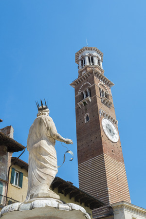 dei: Low angle shot of Torre dei Lamberti in Piazza delle Erbe in Verona, with Marble statue in the foreground.