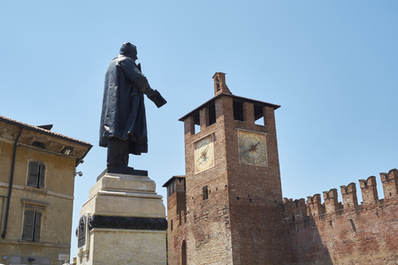 cavour: Statue of Cavour with Castelvecchio clocktower in the background, in Verona, Italy.