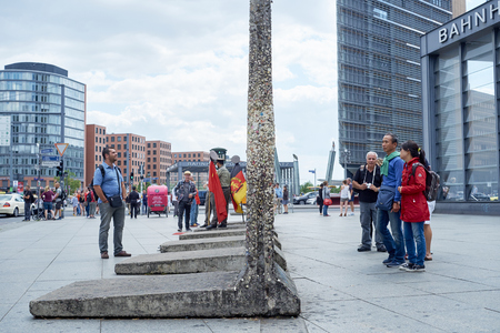 east berlin: BERLIN, GERMANY - JULY 08: Tourists looking at remaining segments of the wall in central East Berlin. July 08, 2015 in Berlin.