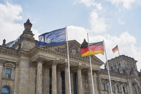 billowing: BERLIN, GERMANY - JULY 08: German and EU flags blowing in the wind in front of the Reichstag building. July 08, 2015 in Berlin.