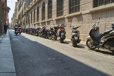 low  angle: VERONA, ITALY - JULY 13: Low angle shot of street with scooters parked. July 13, 2015 in Verona.