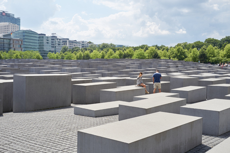 murdered: BERLIN, GERMANY - JULY 08: Young couple seated on stone block at the Memorial to the Murdered Jews of Europe. July 08, 2015 in Berlin. Editorial
