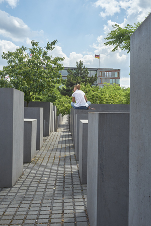 murdered: BERLIN, GERMANY - JULY 08: Young girl seated on stone block at the Memorial to the Murdered Jews of Europe. July 08, 2015 in Berlin.