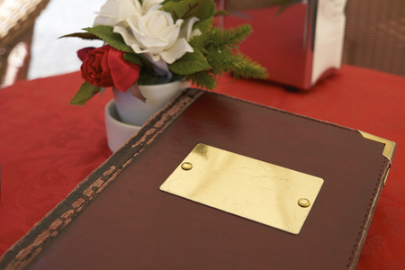 cropped out: Detail of leather bound menu with blank name plate on red table cloth. Theres a small flower vase on the side with red and white roses.