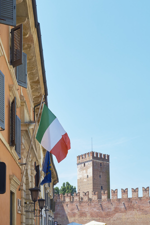 billowing: Italian flag billowing in the window, with Castelvecchio tower in the background. Editorial