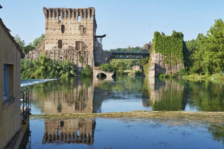 bucolic: BORGHETTO, ITALY - JULY 11: Ruin of tower at Visconteo bridge coasted by river Mincio. July 11, 2015 in Borghetto. Editorial