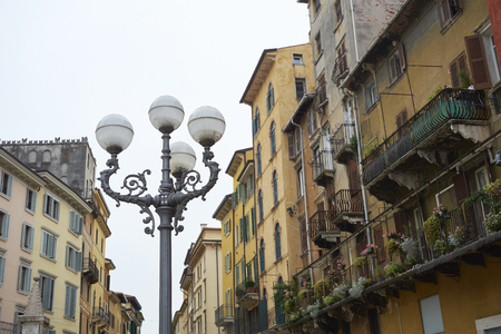 low angle: VERONA, ITALY - JULY 13: Low angle shot of lamp post in Piazza delle Erbe. July 13, 2015 in Verona.