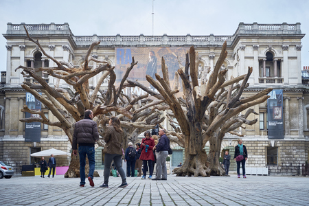 appreciating: LONDON, UK - SEPTEMBER 23: Visitors appreciating Ai Wei Weis installation Tree in the forecourt of the Royal Academy of Arts. September 23, 2015 in London.