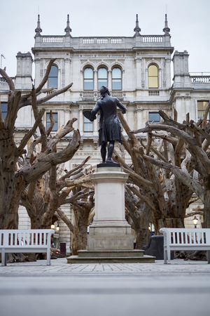 LONDON, UK - SEPTEMBER 23: Statue of Sir Joshua Reynolds amongst Ai Wei Weis installation Tree in the forecourt of the Royal Academy of Arts. September 23, 2015 in London.