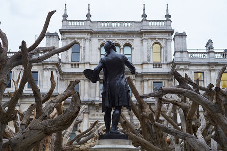 reynolds: LONDON, UK - SEPTEMBER 23: Statue of Sir Joshua Reynolds amongst Ai Wei Weis installation Tree in the forecourt of the Royal Academy of Arts. September 23, 2015 in London.