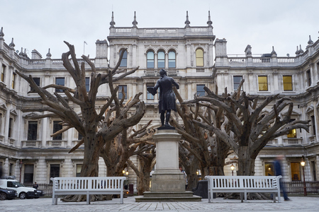 wei: LONDON, UK - SEPTEMBER 23: Statue of Sir Joshua Reynolds amongst Ai Wei Weis installation Tree in the forecourt of the Royal Academy of Arts. September 23, 2015 in London.