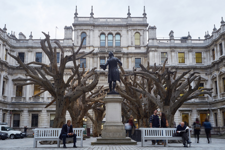 wei: LONDON, UK - SEPTEMBER 23: Visitors appreciating Ai Wei Weis installation Tree in the forecourt of the Royal Academy of Arts. September 23, 2015 in London.