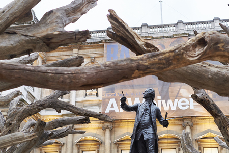 wei: LONDON, UK - SEPTEMBER 23: Statue of Sir Joshua Reynolds framed by branches of Ai Wei Weis installation Tree in the forecourt of the Royal Academy of Arts. September 23, 2015 in London.