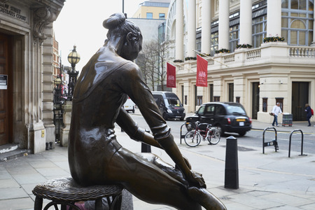 LONDON, UK - DECEMBER 20: Young Dancer statue, by Enzo Plazzotta, with entrance to the Royal Opera House in the background. December 20, 2015 in London.
