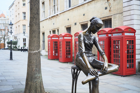 enzo: LONDON, UK - DECEMBER 20: Young Dancer statue, by Enzo Plazzotta, with line of red phone booths in the background. December 20, 2015 in London.