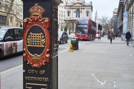 city coat of arms: LONDON, UK - DECEMBER 20: Detail of light post in front of Sommerset House depicting the City of Westminster coat of arms and red double-decker bus in the background. December 20, 2015 in London.