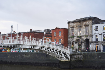liffey: DUBLIN, IRELAND - JANUARY 05: Side view of Hapenny Bridge over Liffey river. The bridge is the main access point to the touristic area of Temple Bar. January 05, 2016 in Dublin Editorial