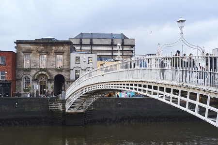 liffey: DUBLIN, IRELAND - JANUARY 05: Perspective view of Hapenny Bridge over Liffey river. The bridge is the main access point to the touristic area of Temple Bar. January 05, 2016 in Dublin
