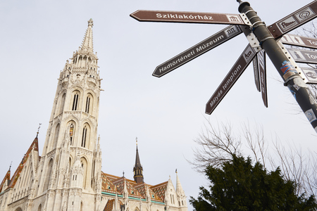castle district: BUDAPEST, HUNGARY - FEBRUARY 02:Low angle shot of directional sign with Saint Matthias Church tower in the background. February 02, 2016 in Budapest. Editorial