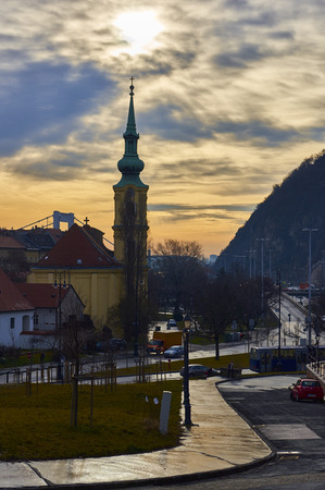 BUDAPEST, HUNGARY - FEBRUARY 02: Sunrise behind clouds over tower of Saint Caitlin of Alexandria Temple. February 02, 2016 in Budapest.