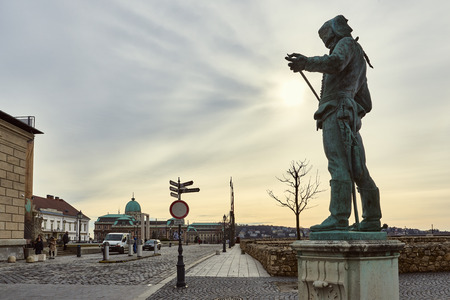 hussar: BUDAPEST, HUNGARY - FEBRUARY 02: Statue of a Hussar inspecting the edge of his sword, with Buda Castle in the background. February 02, 2016 in Budapest.