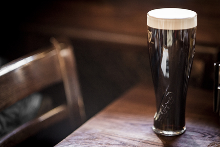 LONDON, UK - MARCH 4: Low key close-up of pint of Guinness on wooden table with empty chair in the background. In London, UK, March 4, 2016.