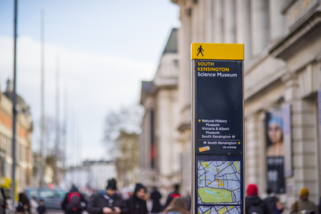 LONDON, UK - MARCH 4: Cropped tourist directional sign in South Kensington with blurred pedestrians in the background. In London, UK, March 4, 2016. Three of the main museums in London are located in South Kensington