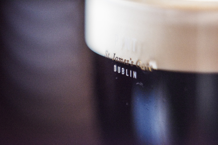 LONDON, UK - MARCH 4: Low key close-up of pint of Guinness featuring the words Dublin and Saint Jamess Gate  on the glass. In London, UK, March 4, 2016.