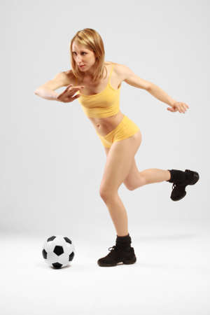 Young girl in yellow is going to kick a ball photo