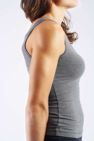 tricep: Young woman with a strong tricep in a gray background Stock Photo