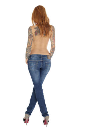 Beautiful woman with tattoos on back and blue jeans photo