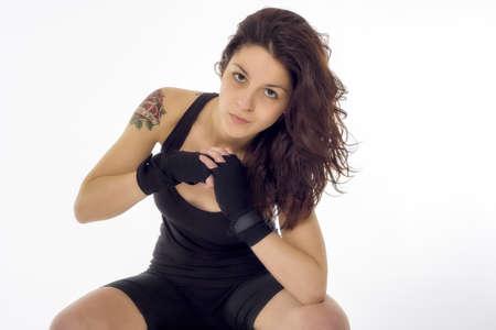 tatoos: Fit female fighter posing in combat poses