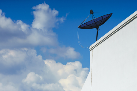 satellite dish stands on the top of a white building with a blue sky and cloudy day. Stock Photo