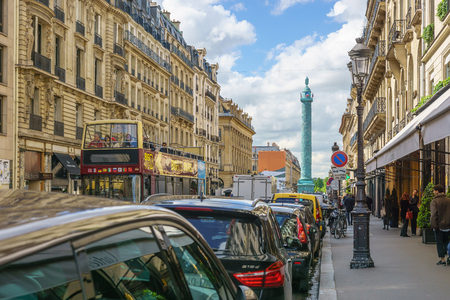 Paris, France - May 2, 2017: The road leading to the Place Vendôme with tourist bus and beautiful architecture on two sides of the street on May 2, 2017, in Paris, France.