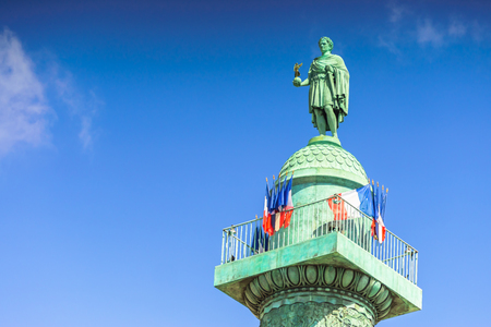 Paris, France - May 2, 2017: Vendome column with statue of Napoleon Bonaparte with blue sky background on May 2, 2017, in Paris, France.