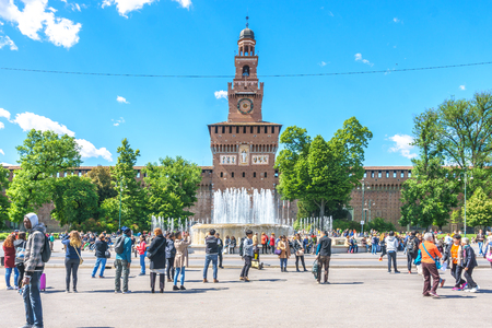 sforzesco: Milan, Italy - April 28, 2017: The Sforzesco Castle main tower behind the fountain with a traveler and blue sky background in Milan, Italy.