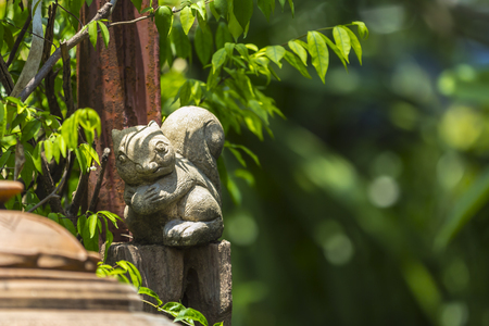 Squirrel stucco doll in the garden with green bokeh background.