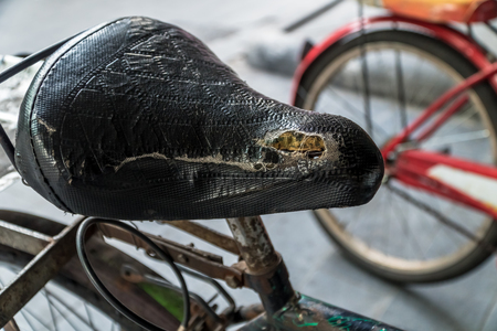 road bike: Close-up shot of old bicycle saddle on an abandoned street.