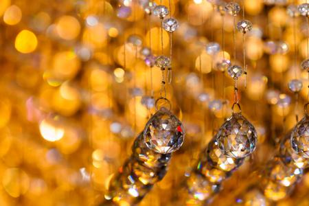 Close-up shot of crystal chandelier decoration with golden light bokeh background.