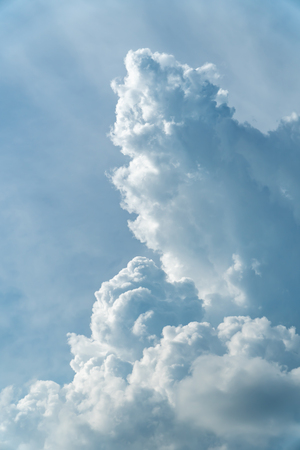 Vertical shot of towering cumulus clouds on blue sky background in an afternoon.