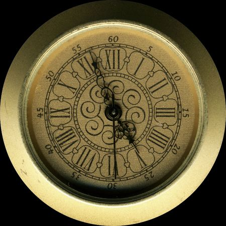 isolated vintage brass clock front panel on black photo