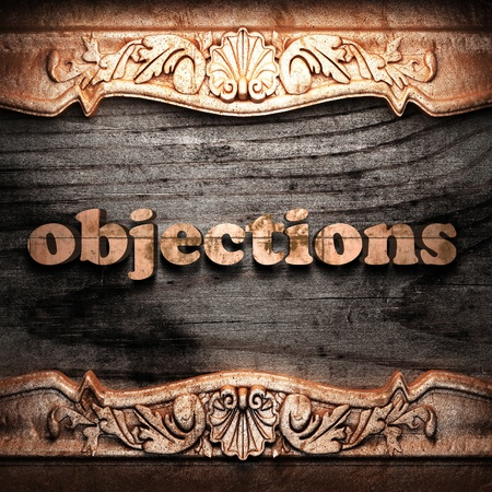 objections: Golden word on wood