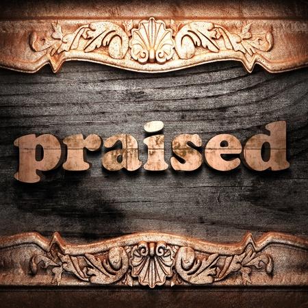 praised: Golden word on wood
