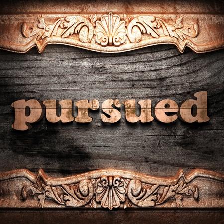 pursued: Golden word on wood